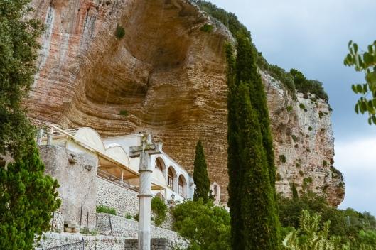 Erst wenn man davor steht, wird das Santuari de Nostra Senyora de Gràcia am Klosterberg Randa unter dem Steilhang sichtbar, Mallorca, Spanien